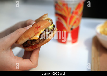 A hand holding a cheese burger with ketchup and soft drink - Stock Image
