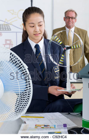 Teacher in background watching female student in school uniform with wind turbine model in science class - Stock Image