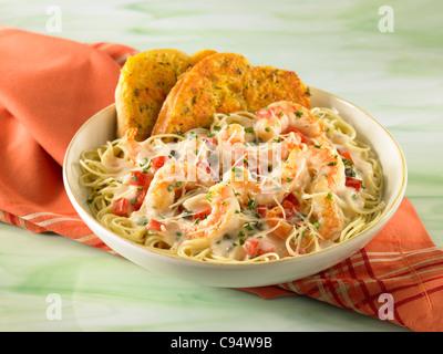 Shrimp Scampi pasta served with garlic bread - Stock Image