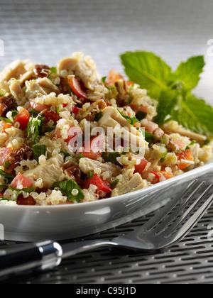 Tuna quinoa salad with tomato, onion, greens and nuts - Stock Image