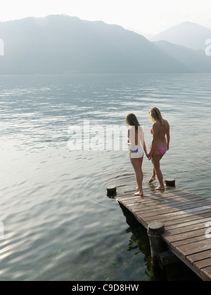 Italy, Piedmont, Lake Orta, Mother and daughter testing water at lake edge - Stock-Bilder
