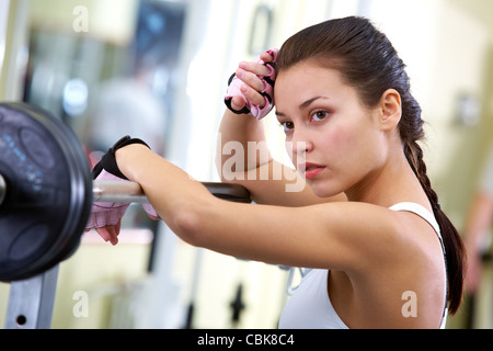 Photo of fit brunette with weightlifting device near by - Stock Image