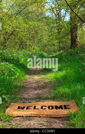Concept photo of a Welcome doormat on a woodland footpath during springtime in vertical format. - Stock-Bilder