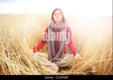 Beautiful young woman meditating in peace radiating light in a long grass field - Stock-Bilder