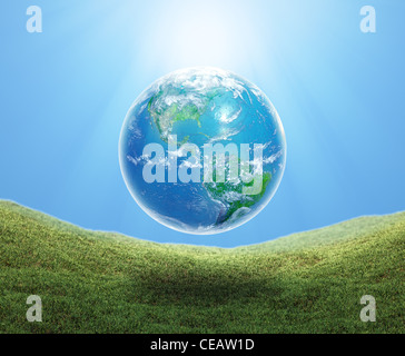 Earth floating over a grass field - Stock Image
