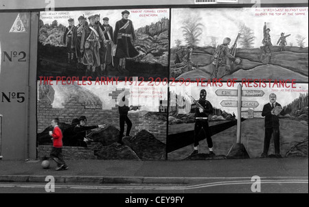 Boy kicking ball past the Shankill Road Mural, Belfast, Northern Ireland, UK, BT13 2AA near Ballysillan - Stock Image