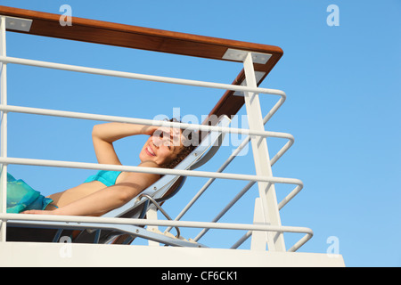 joyful smiling woman wearing swimming suit on deck of cruise ship. - Stock Image
