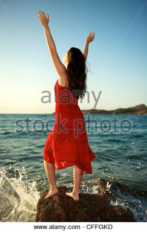 Pretty girl splashing by the wave on the beach at sunset time in Sardinia, Italy - Stock-Bilder