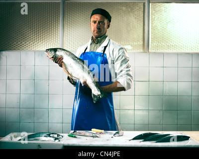 Fishmonger holding a salmon - Stock Image
