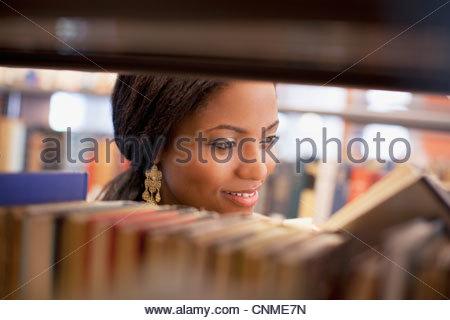 Smiling girl examining book in library - Stock-Bilder