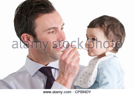 A father feeding his baby son - Stock-Bilder
