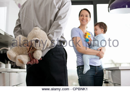 A man returning home to his family after work, holding a teddy bear behind his back - Stock Image