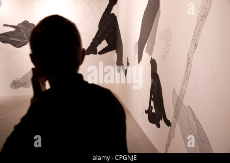 A silhouette of a man looking at an exhibit of the Biennalle di Venezia in Venice, Italy. - Stock Image
