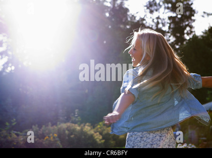 Austria, Teenage girl dancing in sunlight - Stock Image