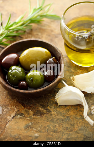 Olive oil and mixed olives with garlic cloves - Stock-Bilder
