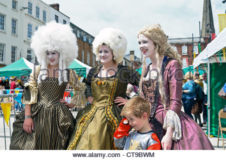 Three young women wearing costumes at Historical Hereford Day, UK. Youth theatre group perform a play outdoors. - Stock Image