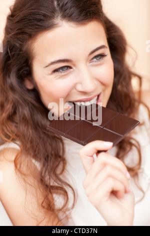 Woman eating chocolate - Stock Image