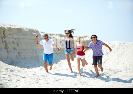 Ecstatic young people running on the sand holding hands - Stock Image