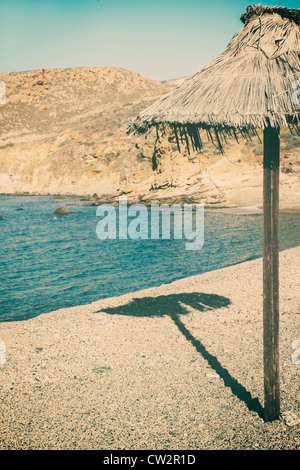 Raffia umbrella on a deserted beach - Stock Image