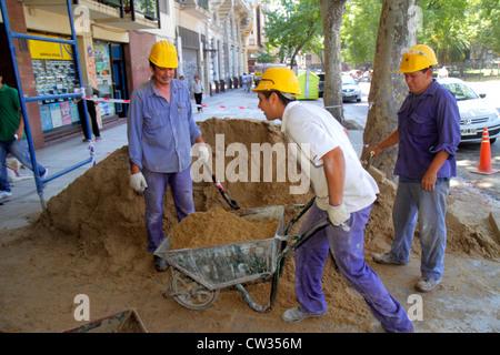 Buenos Aires Argentina Avenida Rivadavia sidewalk construction site Hispanic man worker laborer job hard hat wheelbarrow - Stock Image