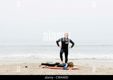 Surfing teacher joking with student - Stock Image