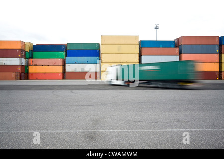 Trucks driving past shipping containers - Stock-Bilder