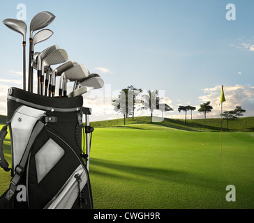 golf equipment on golf course during sunset - Stock Image