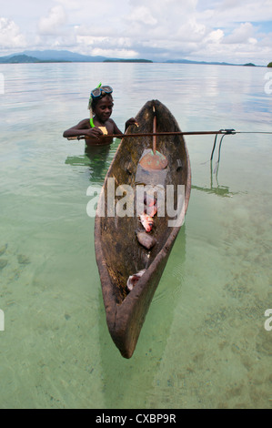 Young boy goes fishing with his canoe and harpoon, Marovo lagoon, Solomon Islands, Pacific - Stock Image