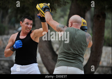 two men practice martial arts in a park - Stock Image