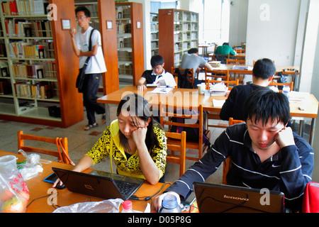 Shanghai China Yangpu District Tongji University Siping Campus Asian man woman teen boy girl student library books - Stock Image