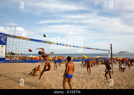 Men playing volleyball on Ipanema beach, Rio de Janeiro, Brazil, South America - Stock Image
