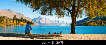 Panorama of a tourist relaxing by Lake Wakatipu in autumn at Queenstown, Otago, South Island, New Zealand, Pacific - Stock Image