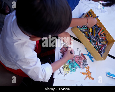 Overhead View Of A Child Coloring With Crayons