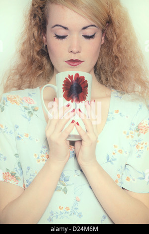 a woman in a floral dress is drinking out of a mug - Stock Image