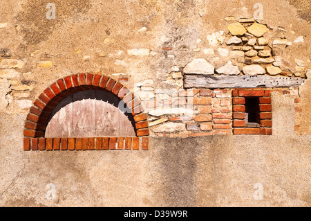 Old brick arch in wall - France. - Stock Image