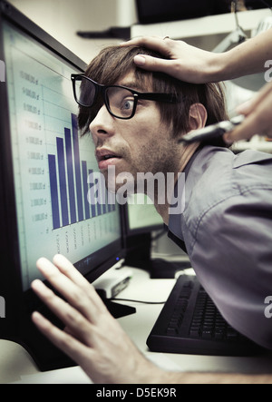 Office worker forced to work harder and harder - Stock Image