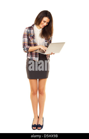 Woman standing while browsing the internet using her laptop - Stock-Bilder