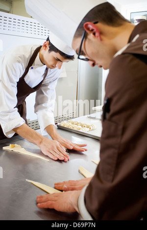 Bakers shaping dough in kitchen - Stock-Bilder