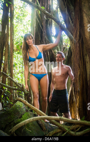 Couple climbing tree in jungle - Stock-Bilder