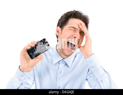 Handsome angry businessman showing broken smartphone with crashed screen. Isolated on white background. - Stock Image