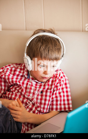 boy using laptop and headphones - Stock-Bilder