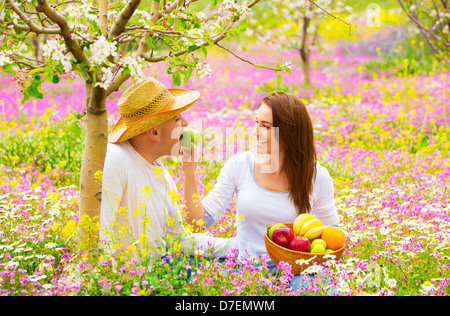Young happy family having fun in spring blooming garden, cute woman feeding her boyfriend apple, romance and love - Stock-Bilder