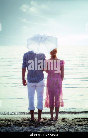 a couple on the beach with a parasol - Stock-Bilder