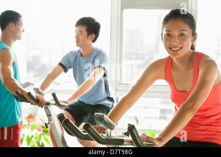 Young people on stationary bikes exercising in the gym - Stock Image