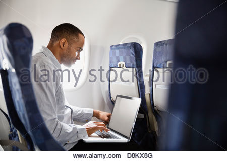 Man using laptop in airplane - Stock-Bilder