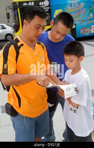 Thailand Bangkok Pathum Wan Rama 1 Road Asian man father boy son teen guide book pointing - Stock Image