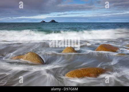 Waves swirl around rocks on Porth Nanven beach, Cornwall, England. - Stock Image