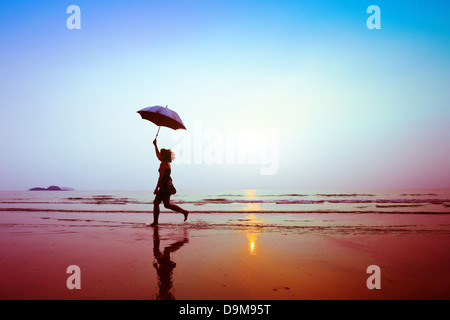 silhouette of happy running woman with umbrella - Stock Image