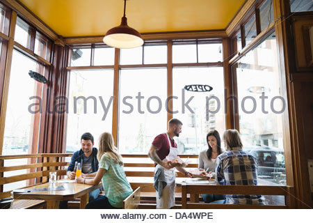 Male deli owner serving food to customers - Stock Image