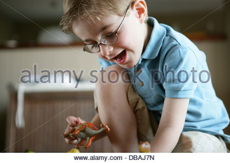Little boy playing with toy dinosaur - Stock Image